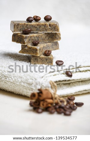 Stack of handmade flavored soap bars with scent of coffee and cinnamon on white towel. - stock photo