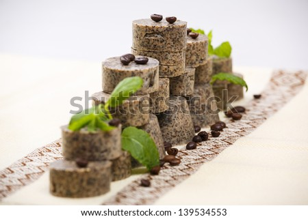 Stack of handmade soap bars with coffee beans and green lavender leafs. - stock photo