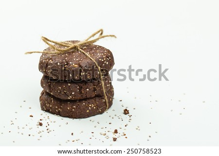 Stack of healthy chocolate, almond and chia seed cookies on white - stock photo