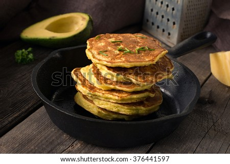 Stack of homemade savory vegetable pancakes / cabbage pancakes / zucchini pancakes / vegetable fritters with cheese. Natural light, selective focus - stock photo