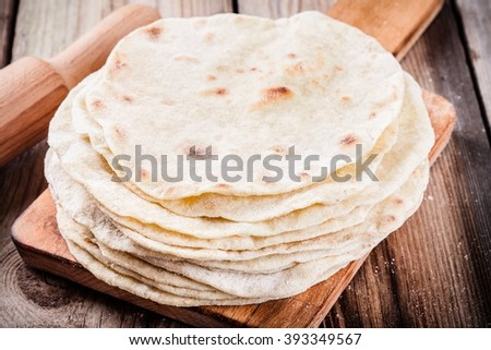 Stack of homemade wheat tortillas on wooden table - stock photo