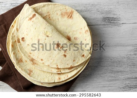 Stack of homemade whole wheat flour tortilla on napkin, on wooden background - stock photo