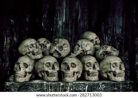 Stack of human skulls on stone table for sacrifice with golden and candle wax - stock photo