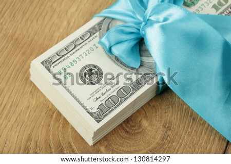 Stack of hundred-dollar bills in a blue gift ribbon - stock photo
