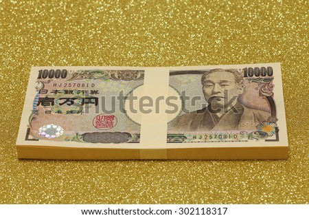 Stack of Japanese money on gold background - stock photo