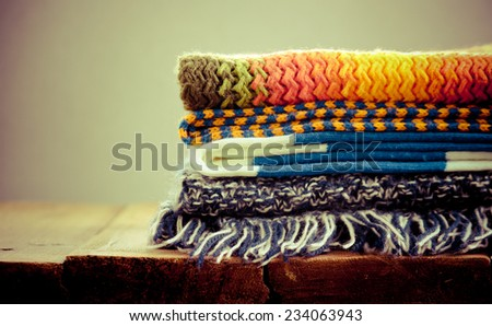 Stack of knitted scarves on a wooden table, retro style - stock photo