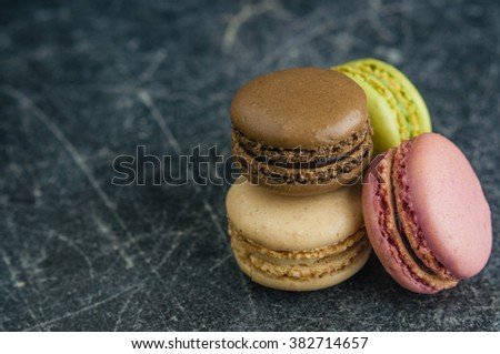 Stack of macaroons on a scratched old chalkboard background, space for text - stock photo