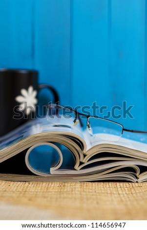 Stack of magazines against blue background - stock photo