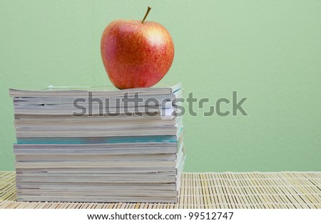 stack of magazines and red apple - stock photo