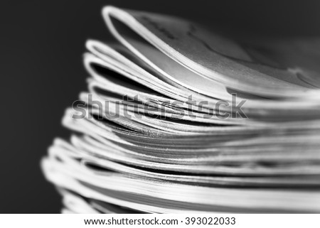 Stack of magazines on black background with swallow depth of field, black and white photo - stock photo