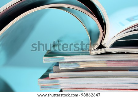 stack of magazines on blue background - stock photo