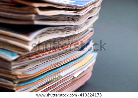 Stack of magazines on dark green background - stock photo