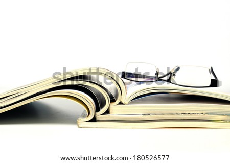 Stack of magazines with nerd glasses - stock photo