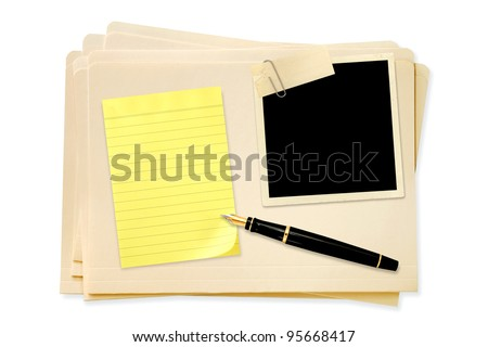 Stack of manila file folders, with blank vintage photo paperclipped, with yellow notepaper and fountain pen. - stock photo