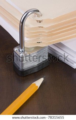 Stack of manila folders closed with a metal lock. - stock photo