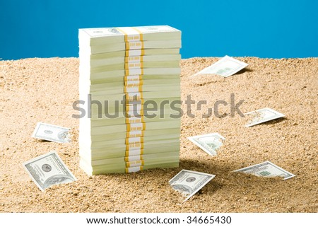 Stack of many hundred dollar banknotes on sand - stock photo