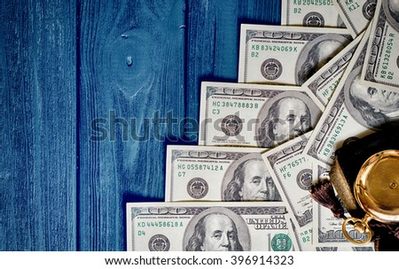 Stack of money dollars laid out like a ladder with antique gold watch on blue retro stylized wood background HDR effect - stock photo
