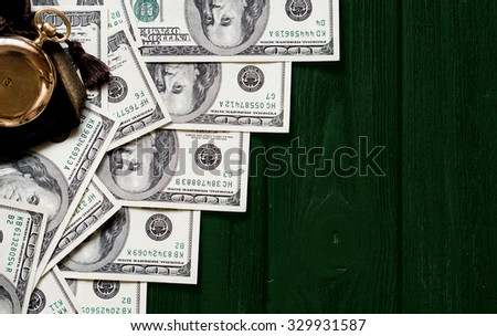 Stack of money dollars laid out like a ladder with antique gold watch on dark green retro stylized wood background - stock photo