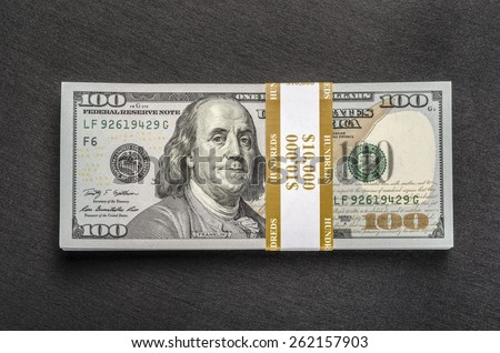 Stack of money wrapped in currency strap - $ 100 one hundred-dollar bills on black background. Top view - stock photo