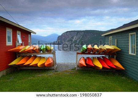 Stack of multicolored kayaks on the shore in beautiful landscape - stock photo