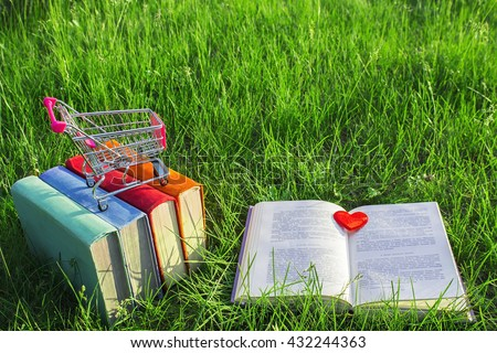 Stack of multicolored old books and open book on the grass at nature, small cart, outdoor office. E-book library and bookstore concept. Business ideas. The love of books. Buying books. Close-up view.  - stock photo
