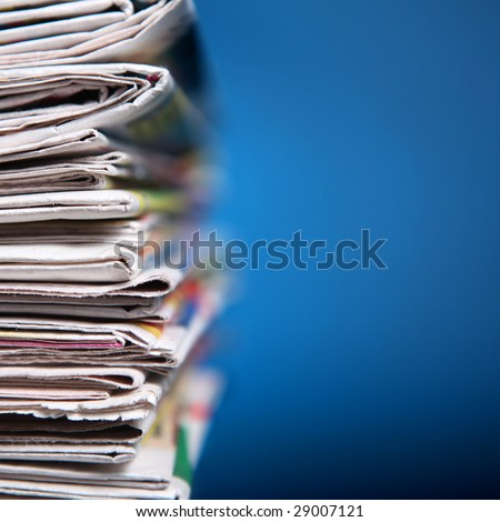 Stack of newspaper on blue background - stock photo