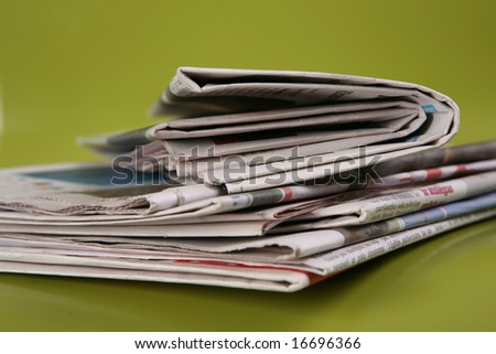 stack of newspaper on green background, close up - stock photo