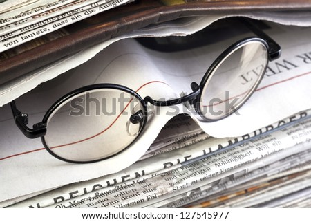 stack of newspaper with reading glasses - stock photo