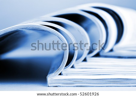 Stack of newspapers lying on the table blue toned - stock photo