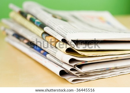 Stack of newspapers lying on the table on green background - stock photo