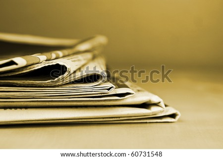 Stack of newspapers lying on the table sepia toned - stock photo