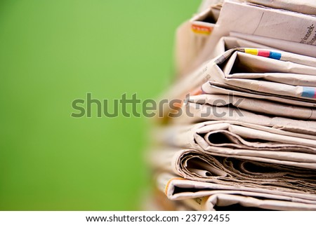 Stack of newspapers on green background - stock photo