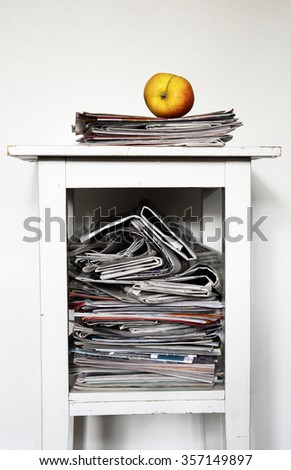 stack of newspapers on the table and an apple - stock photo