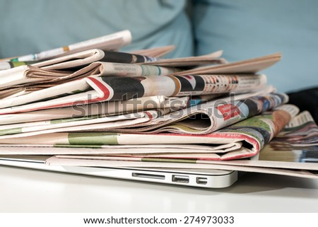 Stack of newspapers, placed on a laptop - stock photo