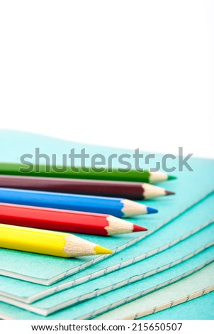 Stack of notebooks and colorful pencils isolated on white - stock photo