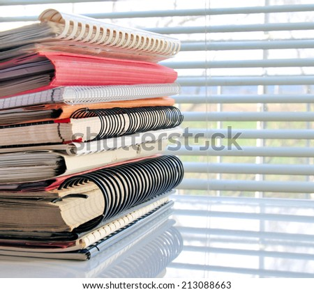 Stack of office folders and ring binders in front of a window - stock photo
