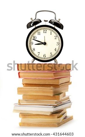 Stack of old books and magazines with alarm clock - stock photo