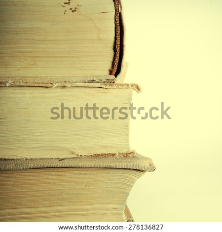 Stack of old books on light grey background.Copyspace on right. Square toned image, instagram effect  - stock photo