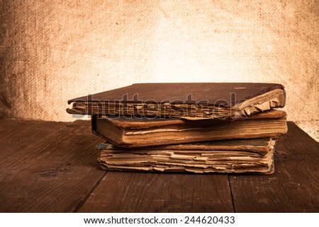 Stack of old books on the old wooden table. - stock photo