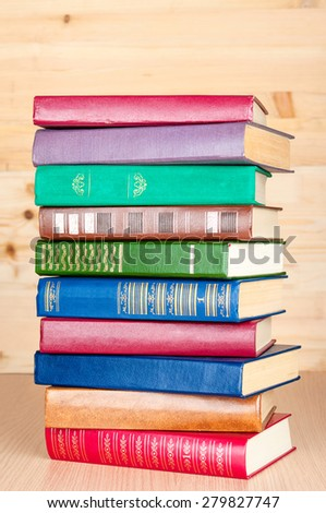 Stack of old books on wooden shelf - stock photo