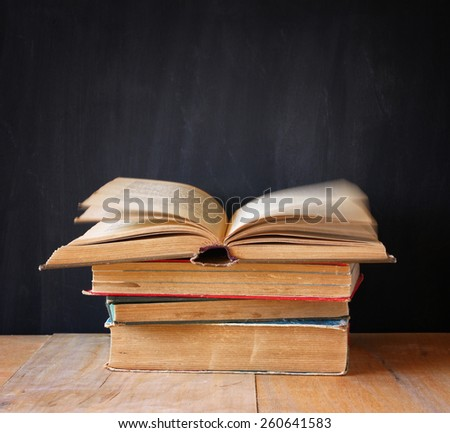 stack of old books, top book is open and pages are in motion, over wooden table and wooden background - stock photo
