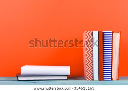 Stack of old hardback books, diary, on wooden deck table and red background. Books stacking. Back to school. Copy Space. Education background. - stock photo
