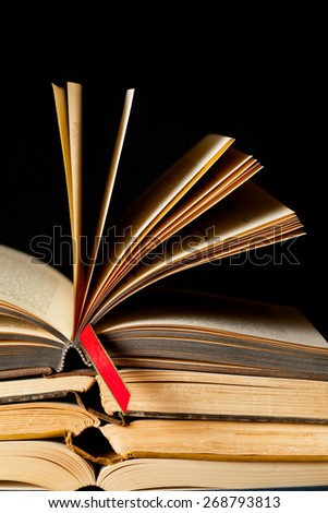 Stack of old opened books with a red ribbon place marker. Black background. Close up with copy space. - stock photo