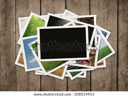 Stack of old photographs at grunge wooden background with clipping path for the blank one - stock photo