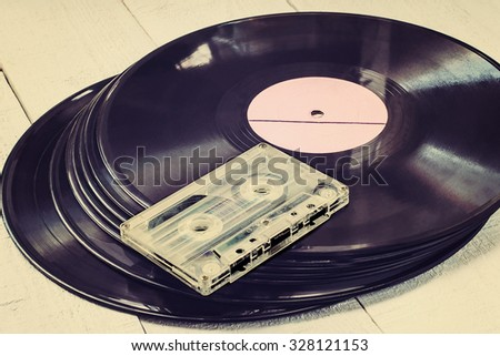 Stack of old vinyl records and audio cassette on white wooden table. Toned photo - stock photo