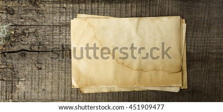 stack of old yellowed paper on wooden board - stock photo