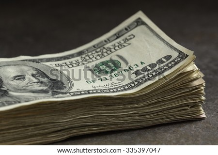 Stack of one hundred dollar bills on a stone table top. Shallow depth of field with focus on Franklin's right eye and corner one hundred. - stock photo