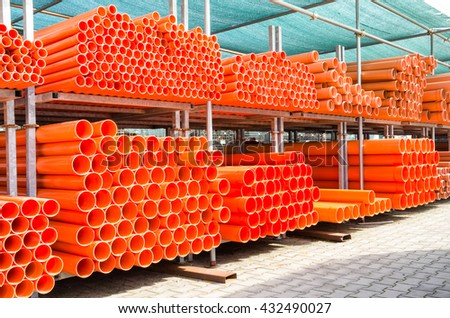 Stack of orange pvc water pipes in abandoned industrial area - Construction concept with plastic equipment pile at building site - stock photo