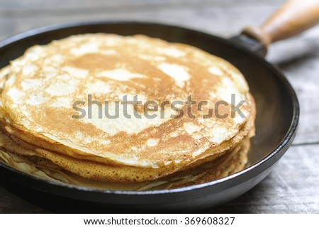 Stack of pancakes on a cast-iron frying pan. Rustic. Shallow DOF - stock photo