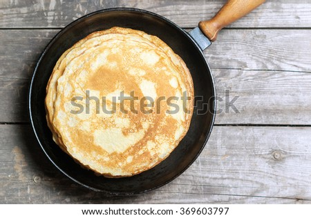 Stack of pancakes on a cast-iron frying pan. Top view. Flat lay - stock photo
